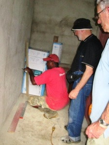 Grant and Allan teaching a Village man how to drill holes for the pipes