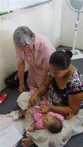 Elizabeth assisting with a lady and her baby with the embroidery of the crosses