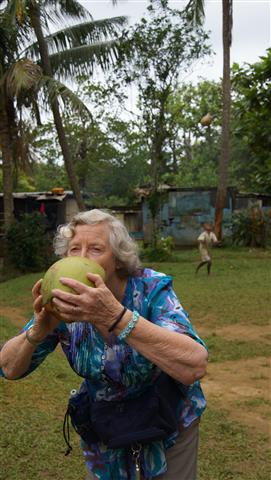 Helen experiences 'real coconut milk' freshly offered by a squatter village we were visiting