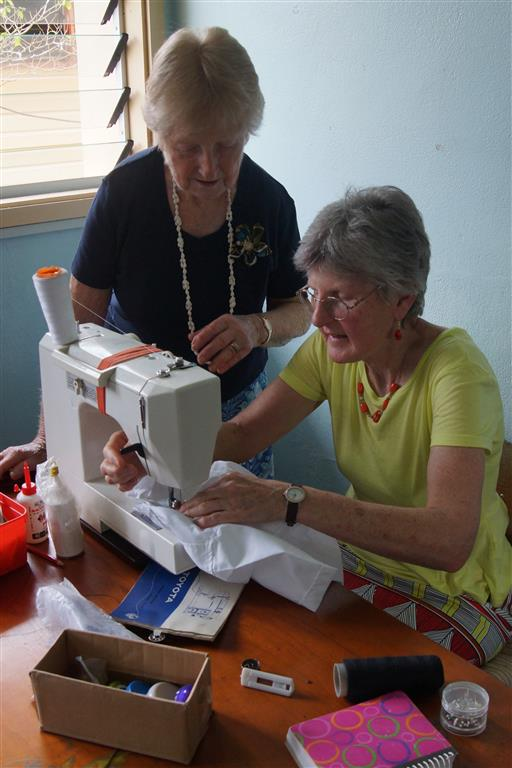 Norma (standing) and Elaine sewing blouses for the girls
