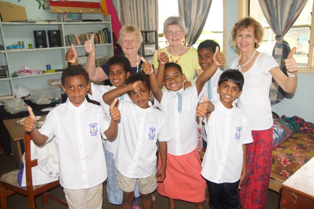Norma, Elaine and Jane (who organised the sewing machines) with the children display their newly sewn blouses and sulu's