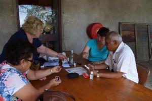 Archbishop Winston having his health check by Archer nurses Adele and Anita, with Principal Amy watching on
